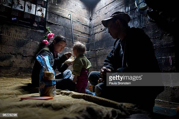 Nandintsetseg feeds their son Munkhorgil, 18 months, before going to work, as father, Baigalnaa watches living inside the small sewer that the family...
