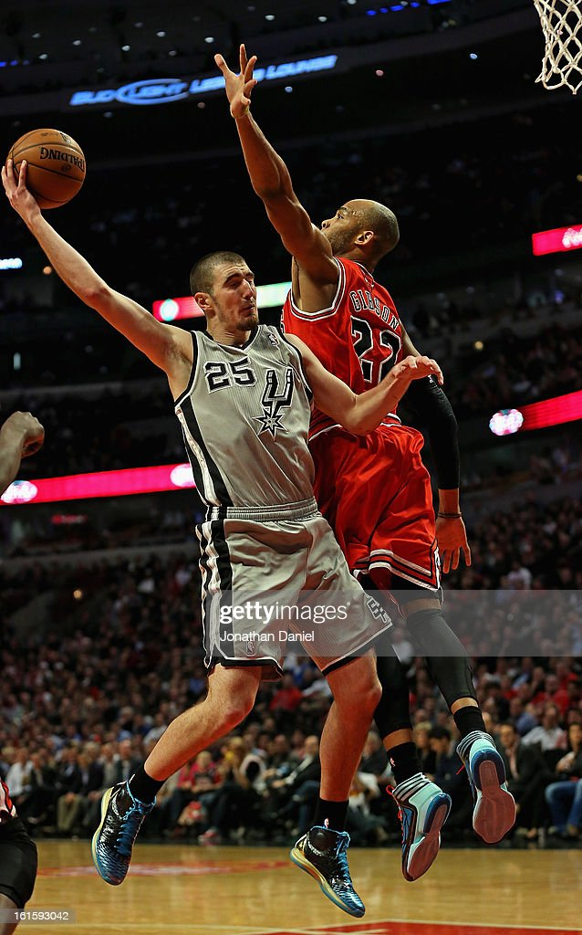 Nando De Colo #25 of the San Antonio Spurs passes the ball around Taj Gibson #22 of the Chicago Bulls at the United Center on February 11, 2013 in Chicago, Illinois. The Spurs defeated the Bulls 103-89.