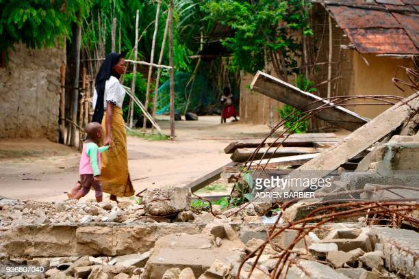 Nanduadua residents walk past the rubble and debris of a Mosque allegedly destroyed by Mozambican Government Security Forces following a twoday...