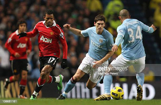 Nani of Manchester United clashes with Gareth Barry and Nigel De Jong of Manchester City during the Barclays Premier League match between Manchester...