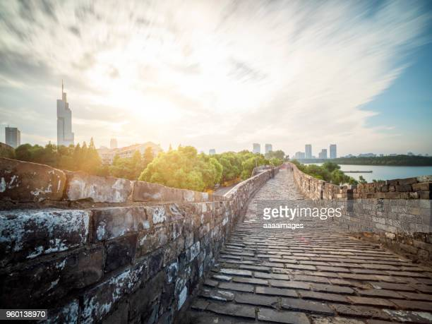 nanjing ancient city wall front of city skyline - fortified wall stock photos and pictures