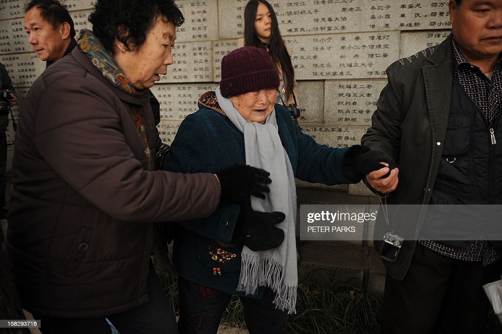 A Nanjing massacre survivor (C) cries after placing flowers on a wall with the names of victims on the 75th anniversary of the Nanjing massacre at the Memorial Museum in Nanjing on December 13, 2012. Air raid sirens sounded in the Chinese city of Nanjing on December 13 as it marked the 75th anniversary of the mass killing and rape committed there by Japanese soldiers -- with the Asian powers' ties at a deep low. AFP PHOTO/Peter PARKS