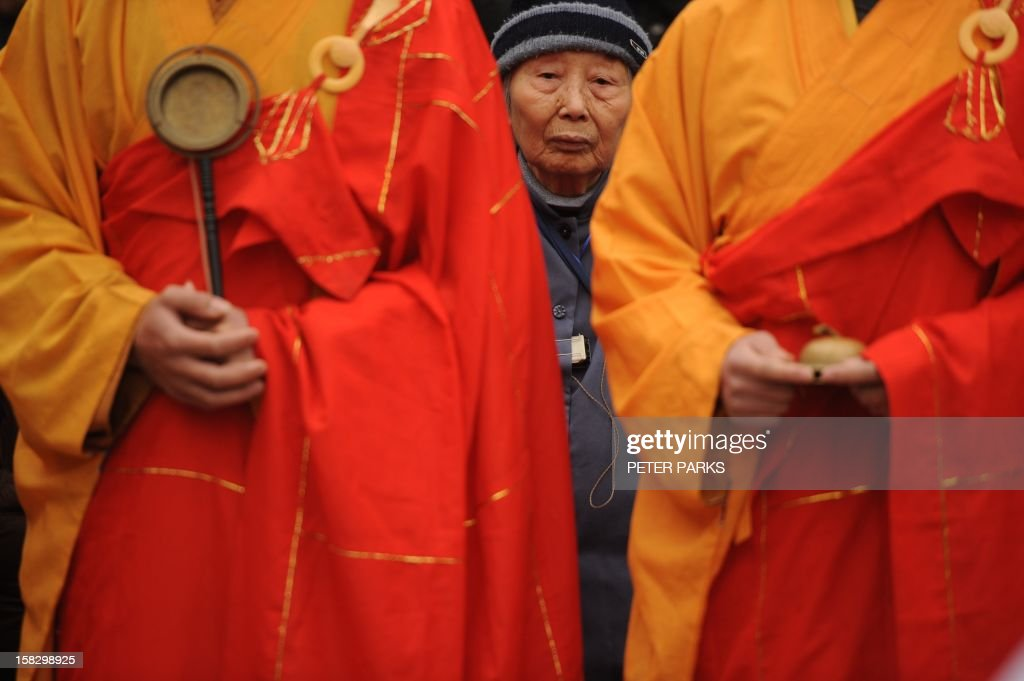 A Nanjing massacre survivor is pictured between Chinese Buddhist monks at a ceremony for the victims on the 75th anniversary of the Nanjing massacre at the Memorial Museum in Nanjing on December 13, 2012. Air raid sirens sounded in the Chinese city of Nanjing on December 13 as it marked the 75th anniversary of the mass killing and rape committed there by Japanese soldiers -- with the Asian powers' ties at a deep low. AFP PHOTO/Peter PARKS