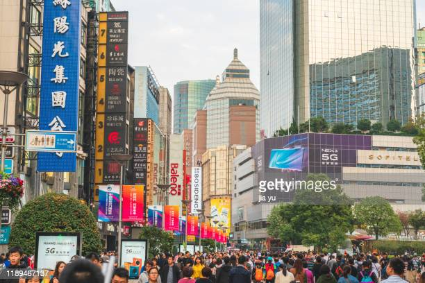 nanjing road pedestrian street crowded traffic flow and billboards, shanghai, china. - nanjing road stock pictures, royalty-free photos & images
