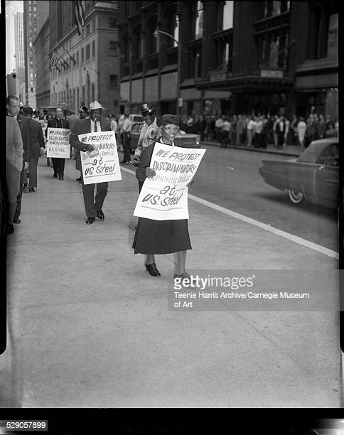 Nannie L Carrington and Houston Dargan carrying signs reading 'We protest discriminatory seniority units at US Steel' with Father Donald McIlvane in...