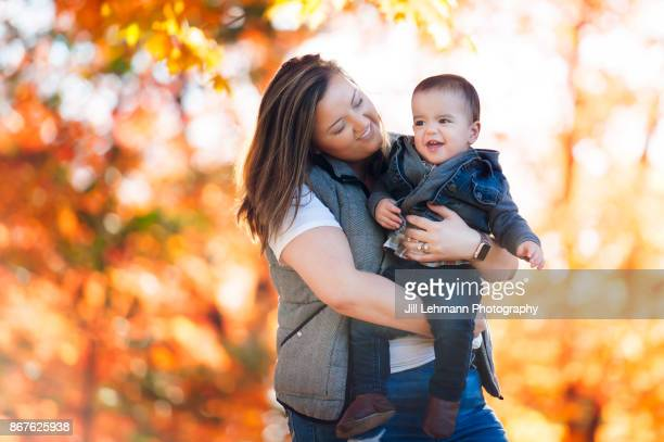Nanny Hugs Toddler at the Iowa State Campus in the Autumn Leaves full of color