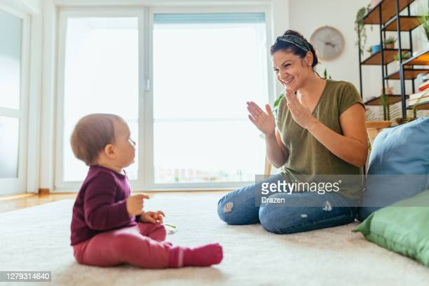nanny playing with baby girl at home - woman showing how to clap to baby - clapping hands stock pictures, royalty-free photos & images