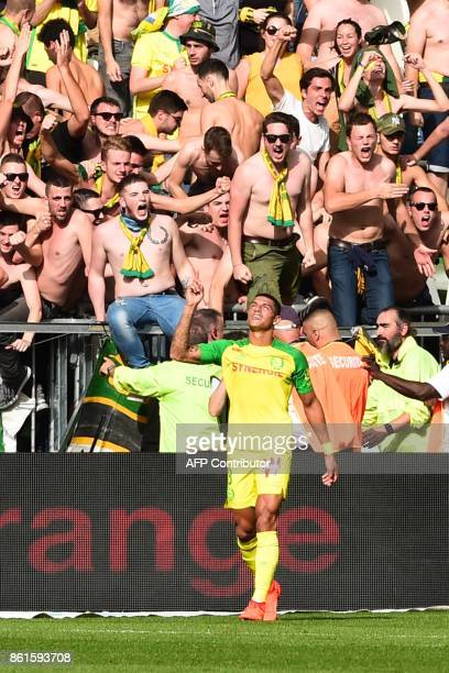 Nantes' Brazilian defender Diego Carlos celebrates next to fans after his team scored a goal during the French Ligue 1 football match between...