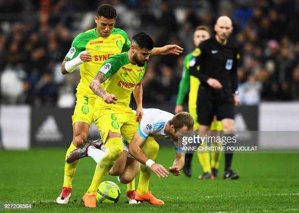 Nantes' Brazilian defender Lima and Nantes' Brazilian defender Diego Carlos vie with Olympique de Marseille's French forward Valere Germain on March...
