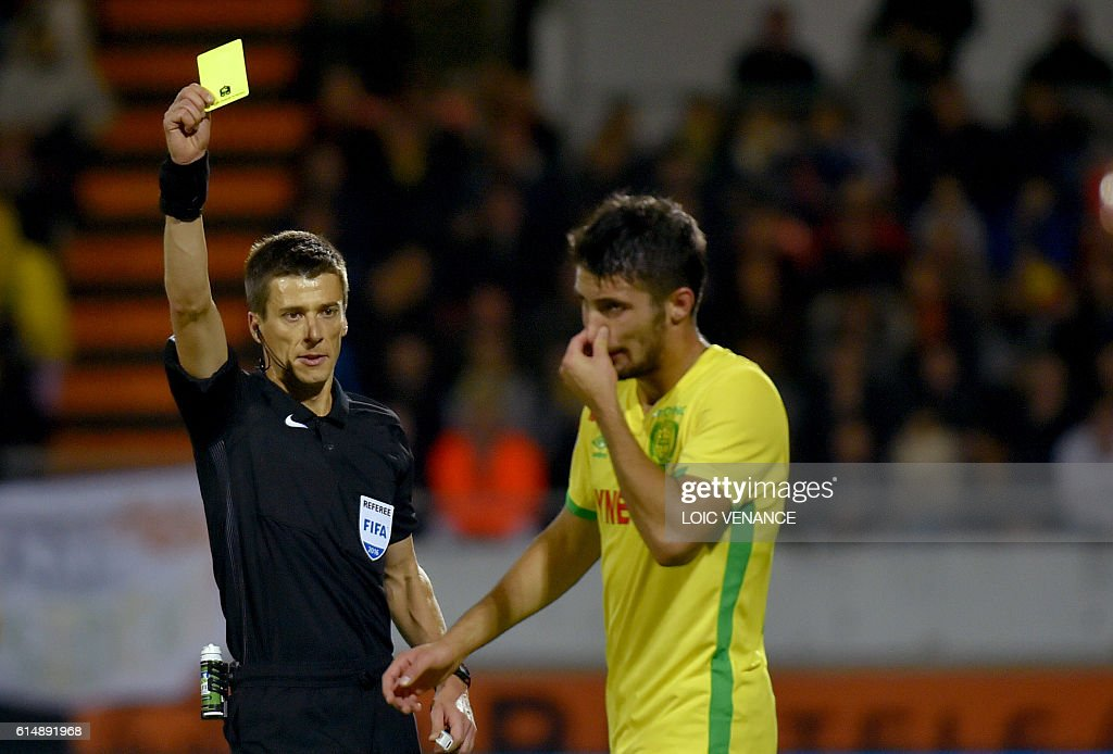 Nantes' French defender Leo Dubois is shown a yellow card by French referee Benoit Bastien during the French L1 football match Lorient vs Nantes, at the Moustoir Stadium in Lorient, western France, on October 15, 2016. / AFP / LOIC