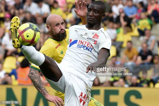 Nantes' French defender Nicolas Pallois vies for the ball with Amiens' French forward Sehrou Guirassy during the French L1 football match between...