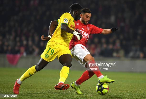 Nantes' French midfielder Abdoulaye Toure vies with Nîmes's French midfielder Jordan Ferri during the French L1 football match between Nimes...