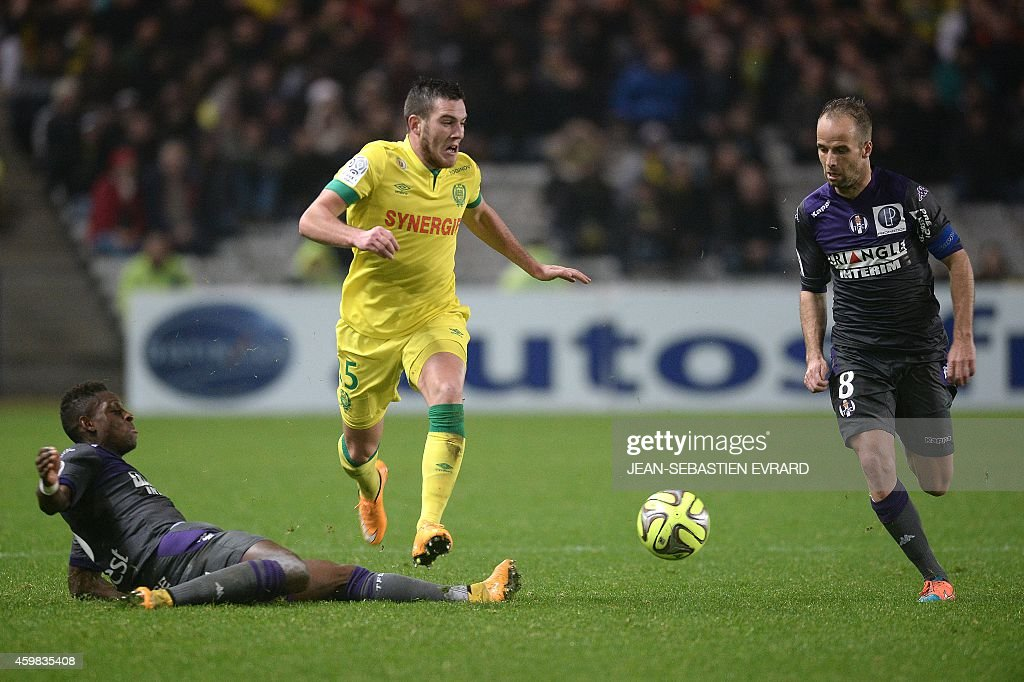Nantes' French midfielder Jordan Veretout is tackled by Toulouse's Swiss defender Jacques François Moubandje during the French L1 football match between Nantes (FCN) and Toulouse (TFC) on December 2, 2014 at the Beaujoire stadium in Nantes, western France.
