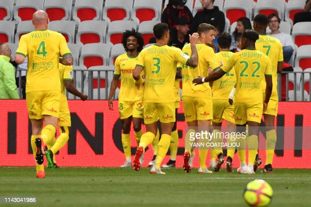 Nantes' French midfielder Samuel Moutoussamy celebrates with teammates after scoring a goal during the French L1 football match between Nice and FC...