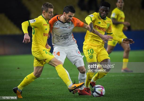 Nantes' Ghanaian forward Majeed Waris and Nantes' French midfielder Valentin Rongier fight for the ball with Montpellier's French defender Damien Le...