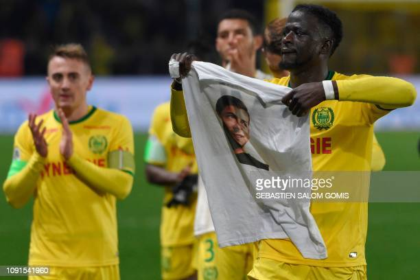 Nantes' Guinean defender Abdoulaye Toure holds a teeshirt depicting Nantes' Argentinian forward Emilianio Sala who is missing following a plane crash...