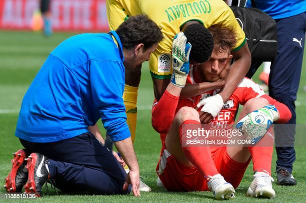 Nantes' Malian forward Kalifa Coulibaly apologises after a collision with Amiens' French goalkeeper Regis Gurtner during the French L1 football match...