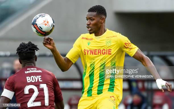 Nantes' Malian forward Kalifa Coulibaly eyes the ball next to Metz' Ghanean defender John Boye during the French L1 football match between FC Metz...