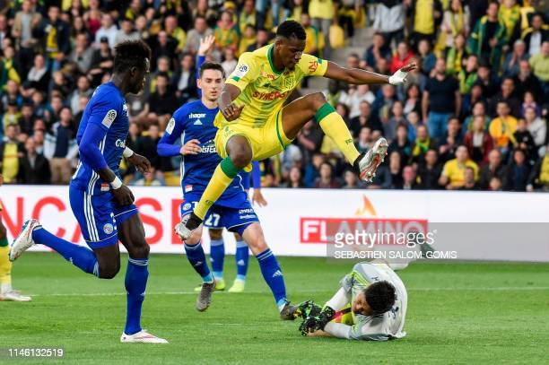 Nantes' Malian forward Kalifa Coulibaly jumps as Strasbourg's Japanese goalkeeper Eiji Kawashima stops the ball during the French L1 football match...
