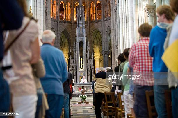 Nantes Mass celebrated in the Basilica of SaintNicolas Believers standing in front of their chair during the church service Priest in the background