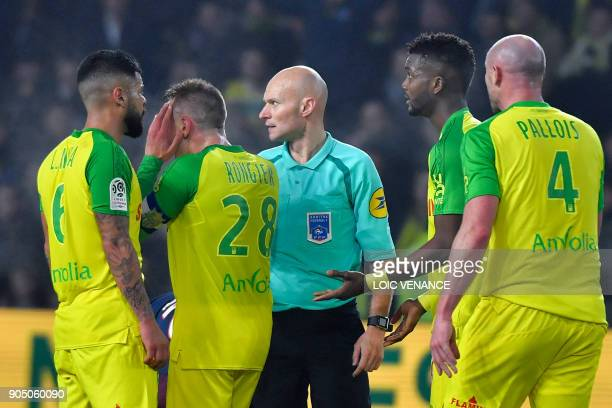Nantes' player argue with French referee Tony Chapron after Brazilian defender Diego Carlos received a red card during the French L1 football match...