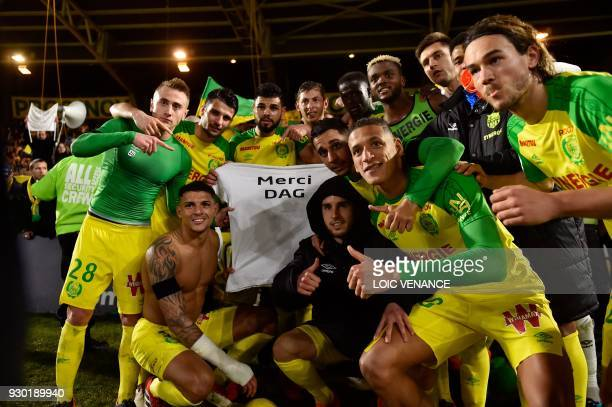 Nantes' players pose with a jersey reading 'Thank you Dag' to pay homage to Nantes' team physiotherapist Philippe Daguillon who died a few days...