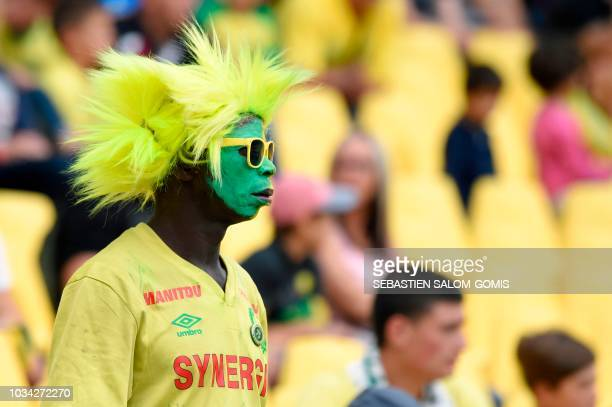 A Nantes' supoorter sporting a yellow wig attends the French L1 football match between Nantes and Reims at the La Beaujoire stadium in Nantes western...