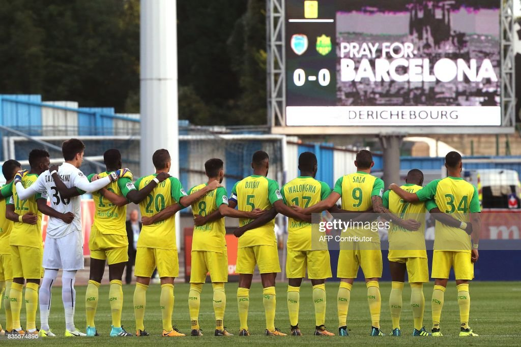 Nantes teammates stand during a minute of silence for the victims of the twin atacks in Spain, prior the French Ligue 1 football match between Troyes and Nantes on August 19, 2017 at the Aube stadium in Troyes. /