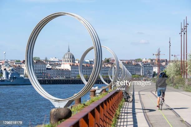 Nantes : The 'Rings' by Daniel Buren on the 'quai des Antilles' , along the Loire river on the ''ile de Nantes' . Cyclist on a cycle lane and...