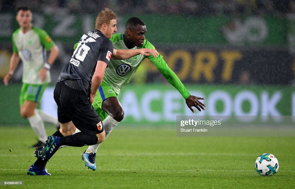Nany Dimata (R) of Wolfsburg and Martin Hinteregger of Augsburg battle for the ball during the Bundesliga match between VfL Wolfsburg and FC Augsburg at Volkswagen Arena on April 13, 2018 in Wolfsburg, Germany.