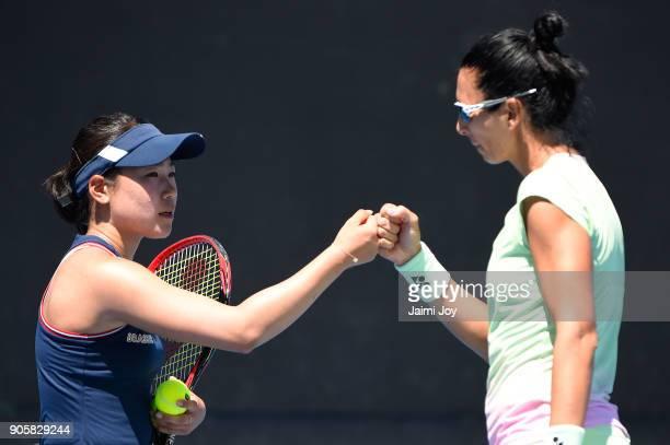 Nao Hibino of Japan and Darija Jurak of Croatia talk tactics in their first round doubles match against Jessica Moore of Australia and Ellen Perez of...