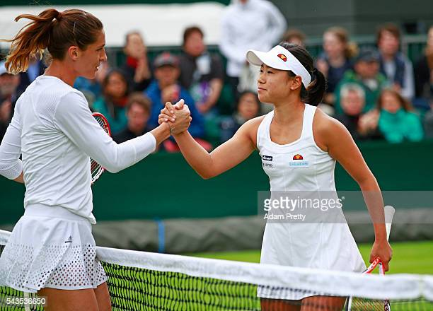 Nao Hibino of Japan shakes hands with Andrea Petkovic of Germany following the Ladies Singles first round match on day three of the Wimbledon Lawn...