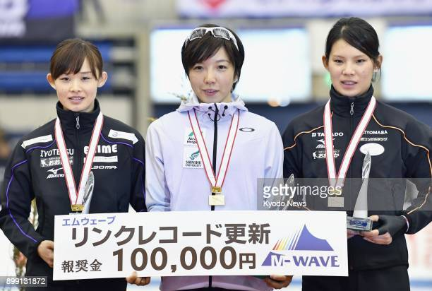 Nao Kodaira winner of the women's 500meter race at an Olympic qualifying meet poses for photos on the podium with secondplace finisher Arisa Go and...
