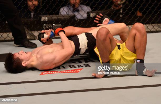 Naoki Inoue of Japan attempts to secure an arm bar submission against Carls John De Tomas of the Philippines in their flyweight bout during the UFC...
