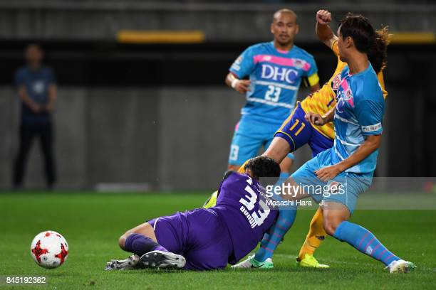 Naoki Ishihara of Vegalta Sendai scores the opening goal while Shuichi Gonda of Sagan Tosu gets injured during the J.League J1 match between Vegalta...