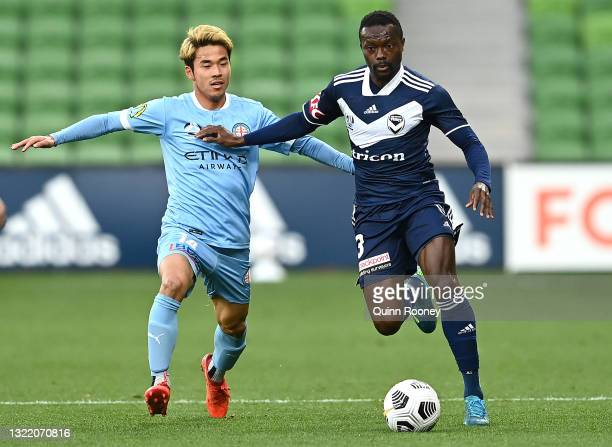 Naoki Tsubaki of Melbourne City and Adam Traore of the Victory compete for the ball during the A-League match between Melbourne Victory and Melbourne...