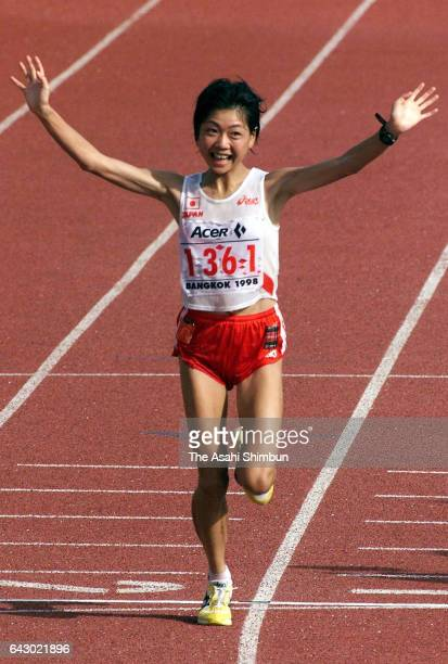 Naoko Takahashi of Japan crosses the finish line to win the gold medal in the Women's Marathon on day zero of the 13th Asian Games at Thammasat...