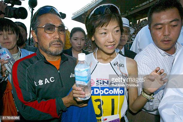 Naoko Takahashi of Japan leaves with her coach Yoshio Koide after the Tokyo International Women's Marathon 2003 at the National Stadium on November...