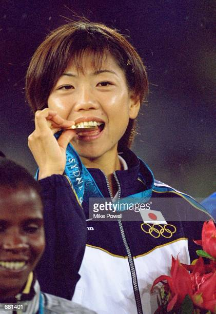Naoko Takahashi of Japan takes a bite of her gold medal on the podium after winning the Women's Marathon at the Sydney Superdome September 24 2000 on...