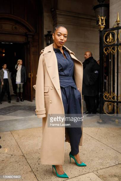 Naomi Ackie wearing Stella McCartney trench coat navy shirt green stilettos and baby blue leather bag outside Stella McCartney during Paris Fashion...