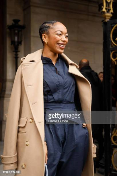 Naomi Ackie wearing Stella McCartney trench coat, navy shirt green stilettos and baby blue leather bag outside Stella McCartney during Paris Fashion...