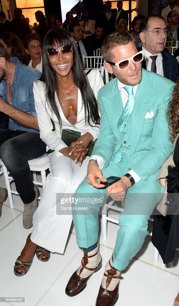 Naomi Campbell and Lapo Elkann watch models walk the runway during the Vogue Fashion Dubai Experience at Dubai Mall on October 10, 2013 in Dubai, United Arab Emirates.