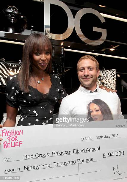 Naomi Campbell gives funds to Red Cross representative Zach Abraham at a Dolce Gabbana flagship store July 16 2011 in London United Kingdom The funds...