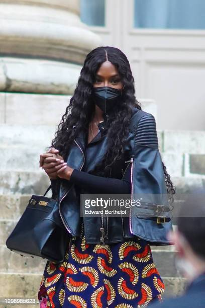 Naomi Campbell is seen wearing a black FFP2 protective face mask, a black leather biker jacket, a black leather bag, jewelry and necklace, a blue and...