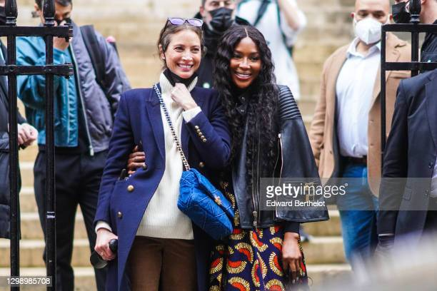 Naomi Campbell is seen wearing a black leather biker jacket, a blue and red dress with printed patterns, black pants ; Christy Turlington wears...