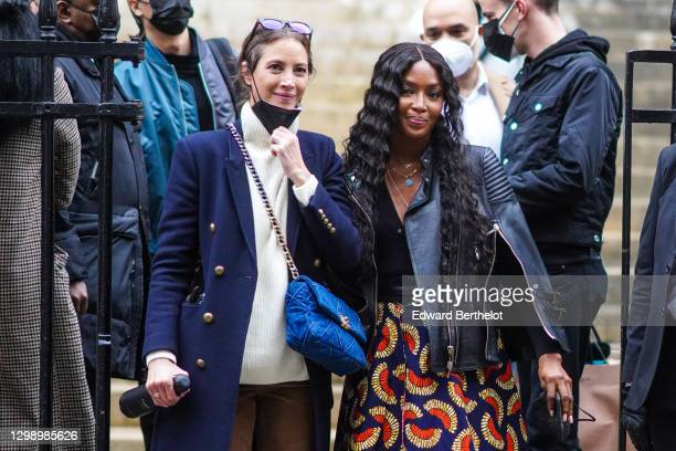 Naomi Campbell is seen wearing a black leather biker jacket, jewelry and necklace, a blue and red dress with printed patterns, black pants ; Christy...