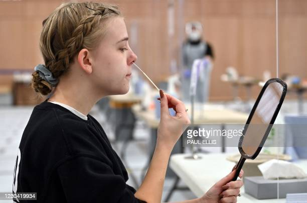 Naomi Carpenter, a 20-year-old sports rehab student at Hull University, takes a swab for a lateral flow Covid-19 test at the campus sports facilities...