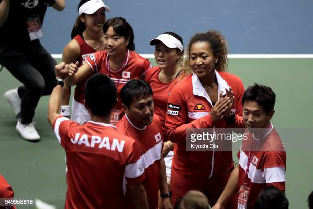 Naomi Osaka of Japan celebrates the team's 32 victory with other members of the Japan Fed Cup team and team staff after the doubles match between...