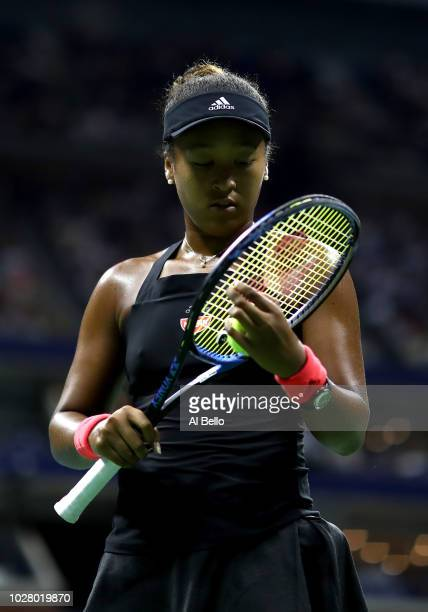 Naomi Osaka of Japan checks her racket during her women's singles semifinal match against Madison Keys of the United States on Day Eleven of the 2018...