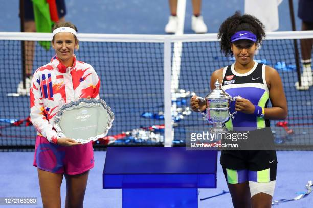 Naomi Osaka of Japan holds the championship trophy and Victoria Azarenka of Belarus holds the finalist trophy after their Women's Singles final match...